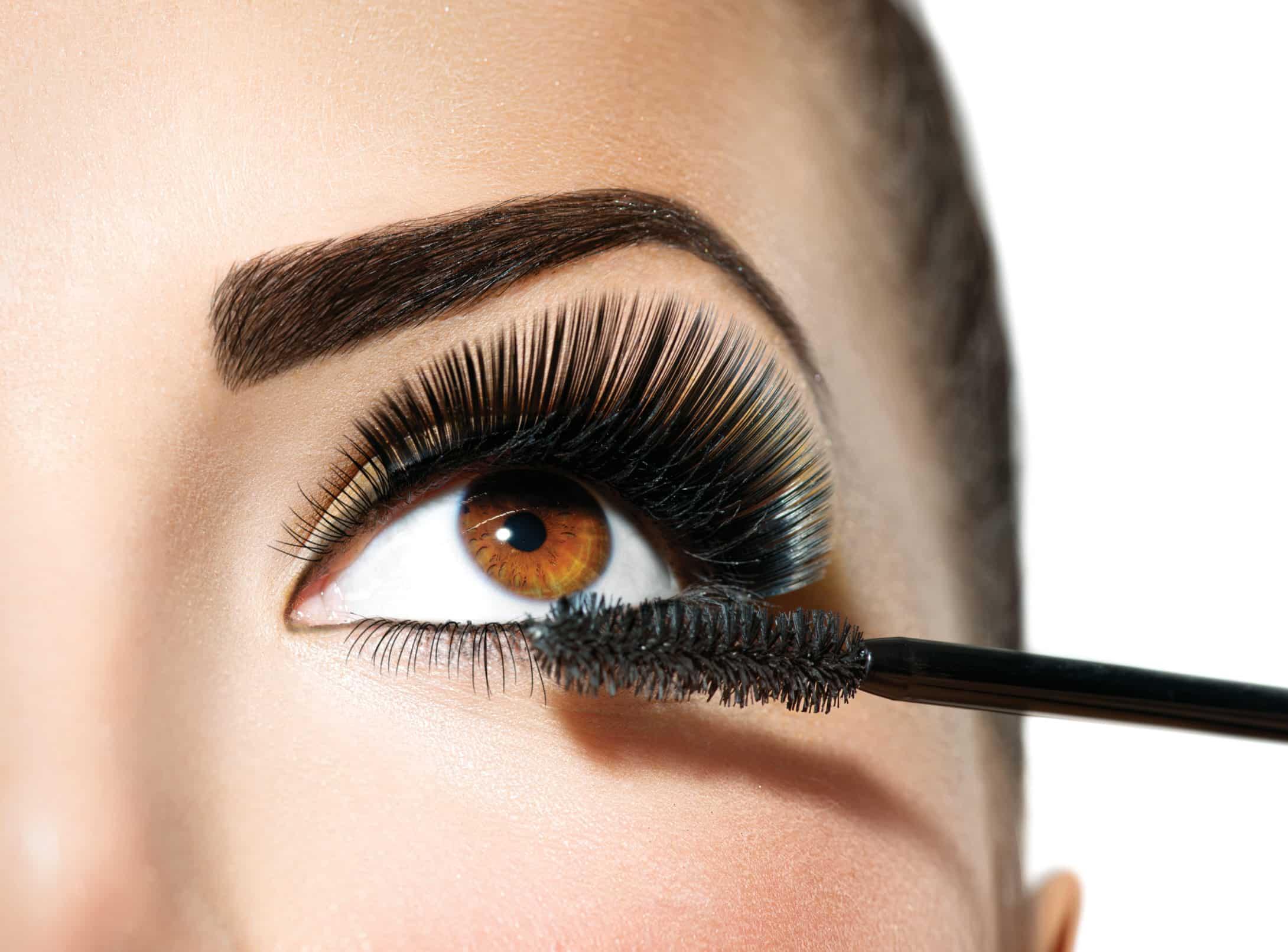Mascara applying. Long lashes closeup. Makeup for brown eyes